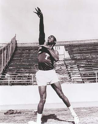 Comedian Bill Cosby throwing the shot put in college.