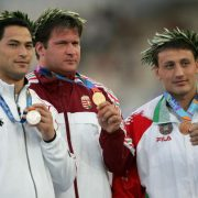 ATHENS - AUGUST 23:  Gold medalist Adrian Annus of Hungary, silver medalist Koji Murofushi of Japan (L) and bronze medalist Ivan Tikhon of Belarus celebrate on the podium during the medal ceremony of the men's hammer throw event on August 23, 2004 during the Athens 2004 Summer Olympic Games at the Olympic Stadium in the Sports Complex in Athens, Greece.  (Photo by Jamie Squire/Getty Images)
