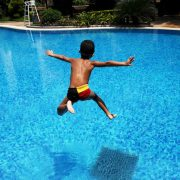 The asian boy jumps into   blue water